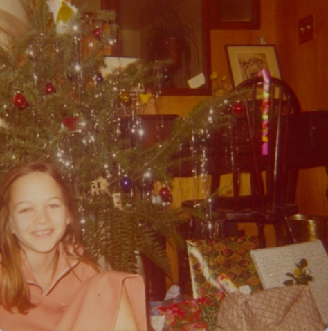 In front of our Charlie Brown Christmas tree Here I am in an ill-fitting thrift store dress, blissfully ignorant of the impending misery.